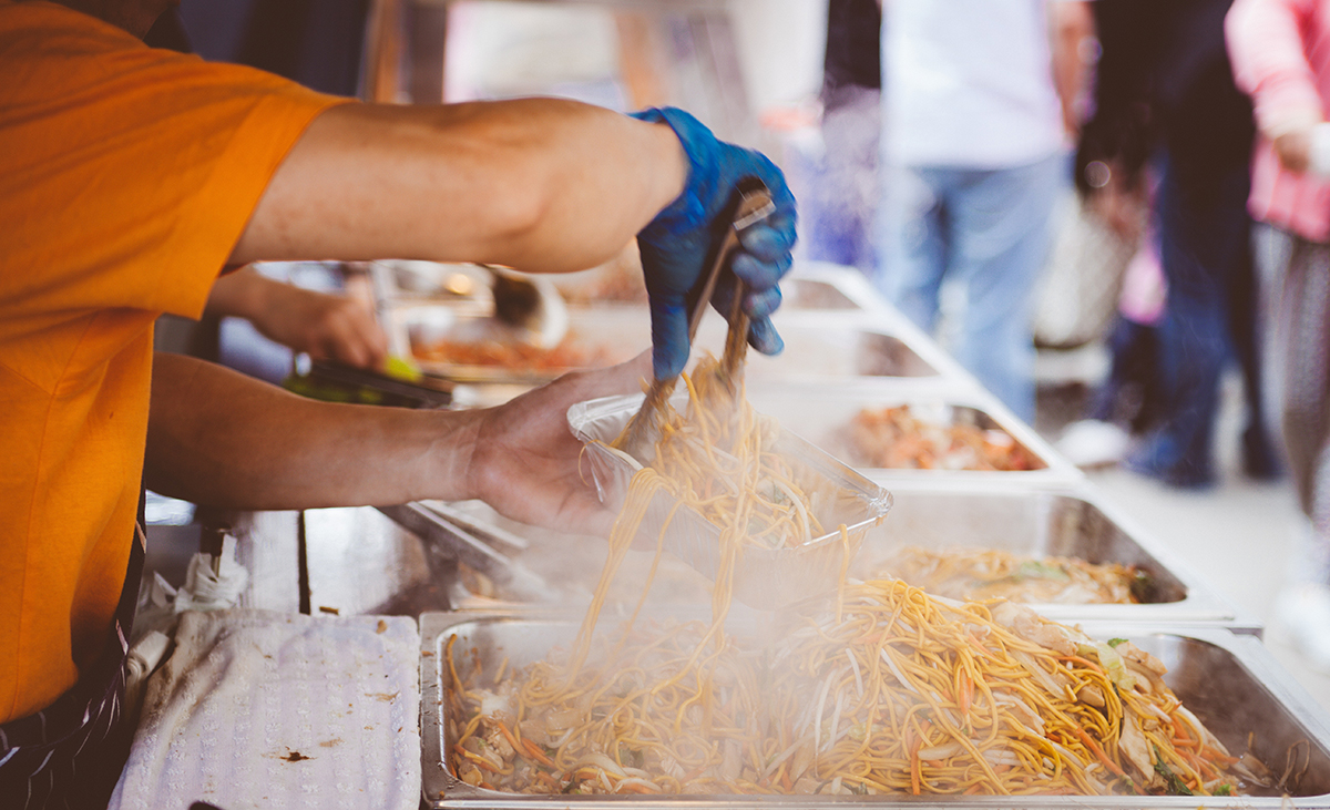 photo of a man serving up noodles at an outdoor event