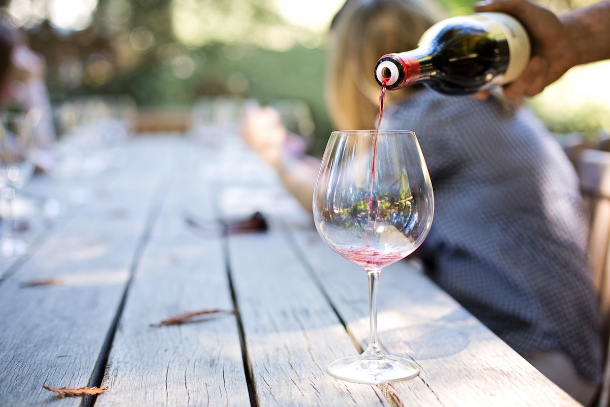 An image of wine being poured into a glass on a picnic table